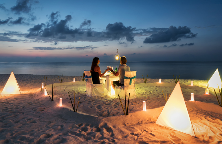 Honeymoon couple is having a private, romantic dinner
